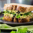 Sandwich ripieno di crema di ceci e avocado con olive e rucola